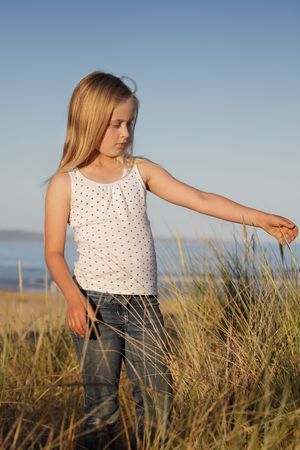 A young girl feels the sea grass at the beach. photo