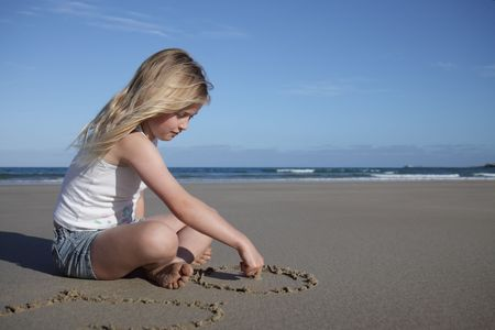 A young girl draws in the sand on the beach. photo