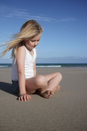 A young girl feels the smooth sand at the beach. photo