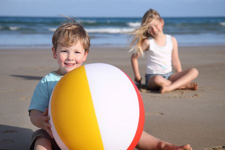 A young boy holds a beach ball on the beach,  girl & ocean in the background. photo