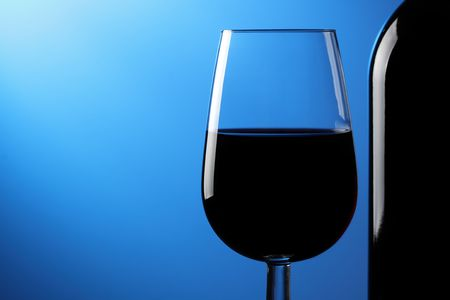 A glass of red wine and bottle on a blue background.
