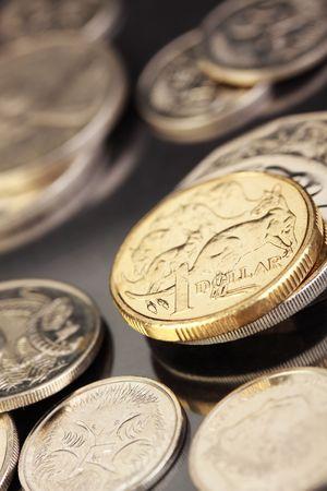 Various australian coins, focus on gold 1 dollar coin.