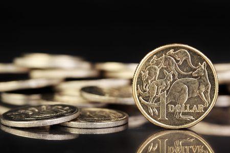 Various australian coins on a dark reflective background.