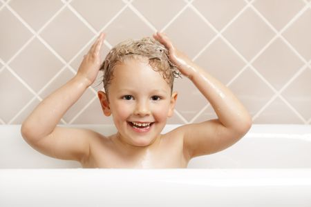 A gorgeous young boy has fun in the bath. Stock Photo