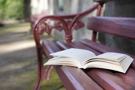 text books: An open book on a park bench seat.