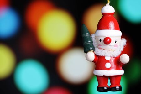 A hand crafted Santa ornament with tree lights background. photo