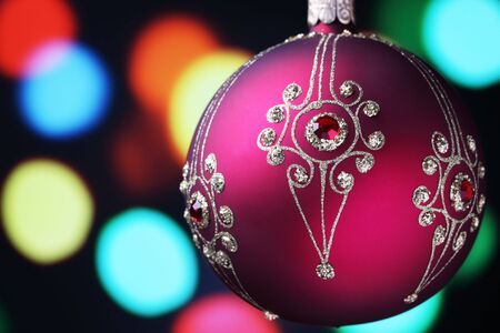 A hand crafted christmas ornament with tree lights background. photo