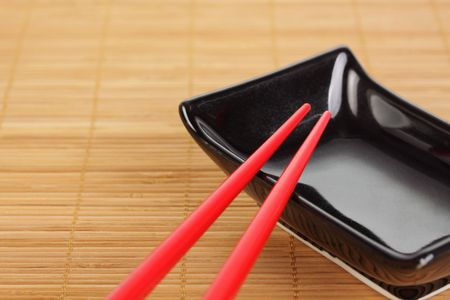 A pair of red chopsticks resting on a small sauce bowl, bamboo mat background. photo