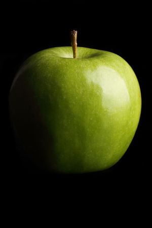 granny smith apple: A fresh Granny Smith apple on a black background.