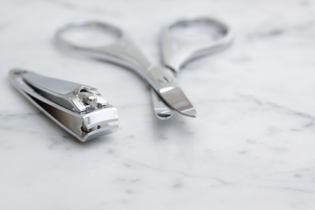 nail scissors: A set of nail scissors & clippers on a marble bench top.