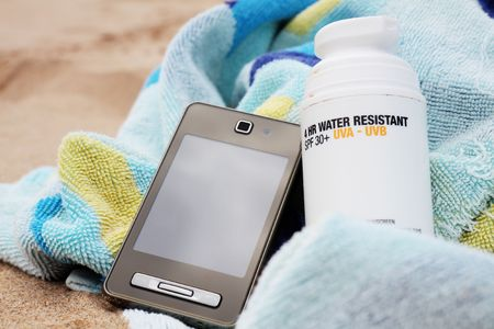 A bottle of sunscreen on a beach towel with mobile phone. Sandy background. photo