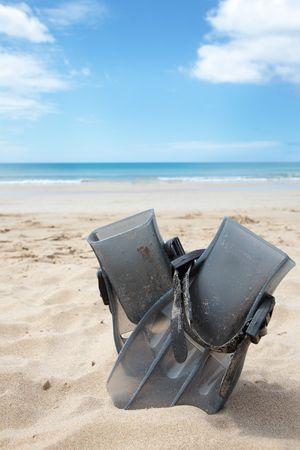 flippers: Aletas buceo superficial en la arena en la playa.
