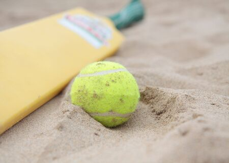 cricket game: A beach cricket bat with tennis ball on the sand.