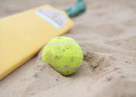 cricket bat: A beach cricket bat with tennis ball on the sand.
