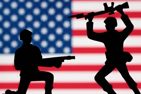 battling: Two toy soldiers battling on an American flag background.