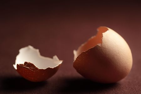cracked egg: A bowl of fresh eggs and cracked egg shells on a dark background.