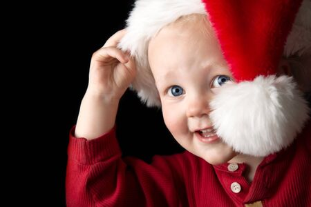 A gorgeous young boy peeking out from behind a santa hat. photo