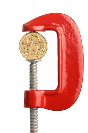vice grip: An Australian dollar coin in a clamp. Financial strain concept.
