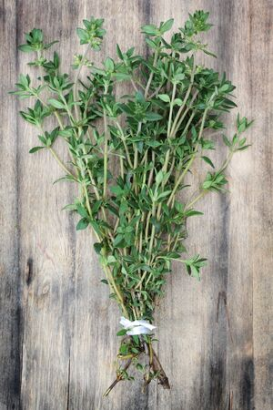 thyme: Verse, biologisch geteelde tijm op een oude houten snijplank.