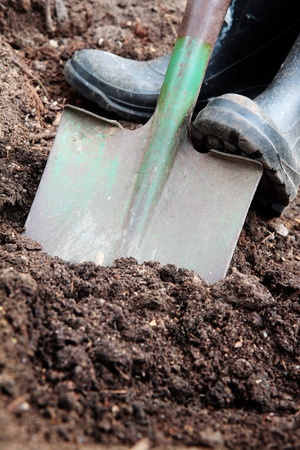 manure: Digging soil with a spade & rubber boots.