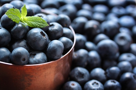 blue berry: Fresh, ripe blueberries in a copper measuring cup.