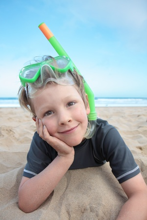 A young boy on the beach with his snorkeling equipment. photo
