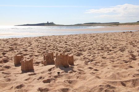 sandcastles: slowly dissolving sandcastles with dunstanburgh in Background