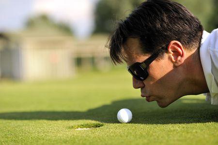Man cheating playing golf Stock Photo