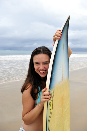 Surf girl holding a board in Brazil photo