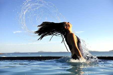 Beautiful swimsuit model splashing water on vacation