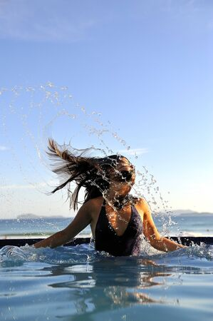 Beautiful swimsuit model splashing water on vacation Stock Photo - 4562878