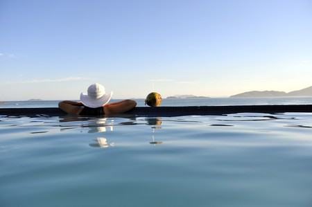 Woman relaxing on a swimming pool with a sea view   photo