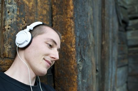 Man listening to the music in a park with white headphones photo