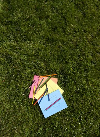 Books and pencils on the grass photo