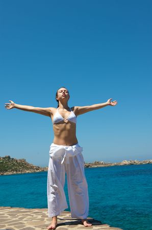 exercice: Pretty woman doing relaxation exercices with a sea view in Sardinia, Italy