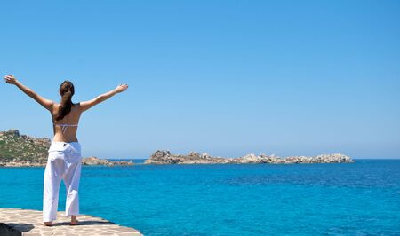 exercices: Pretty woman doing relaxation exercices with a sea view in Sardinia, Italy