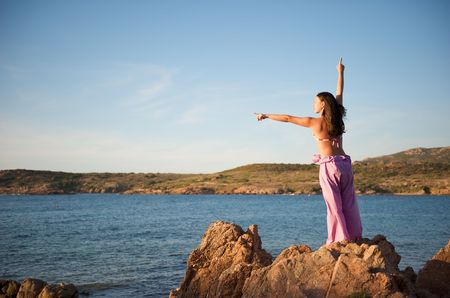 Woman relaxing on the rock with a sea view Stock Photo - 5430137
