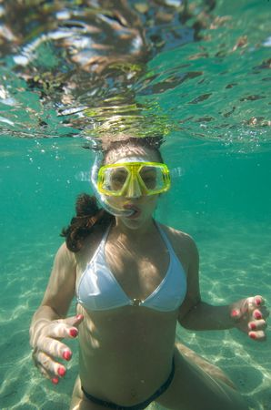 Woman doing snorkeling with goggles and scuba
