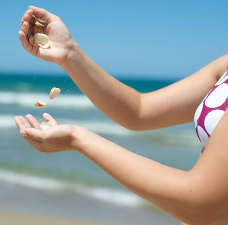 Woman playing with some shells on the beach photo