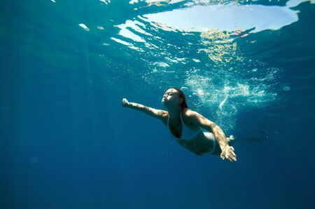 Underwater view of a woman swimming in the ocean photo