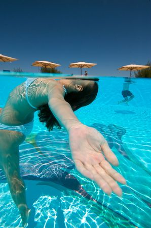 Underwater view of a woman swimming in the swimming pool photo