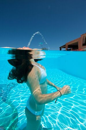 Underwater view of a woman swimming in the swimming pool Фото со стока