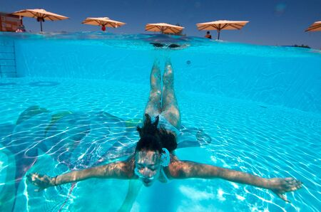 Underwater view of a woman swimming in the swimming pool Stock Photo