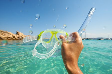 Snorkel equipment in hands against beach and sky with some drops Stock Photo
