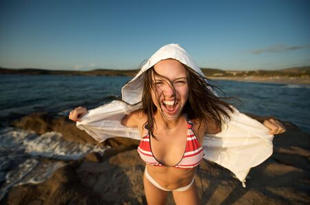 Wonderful pretty girl wearing a bikini screaming on the beach at sunset time photo