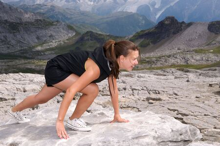 Athletic woman on a rock starting to run  photo