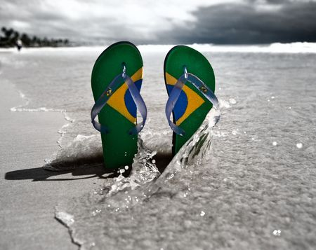 Brazilian flipflop with a coconut on the beach in Brazil
