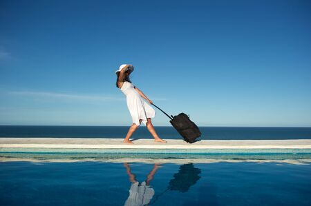 Traveler with heavy baggage walking on a swimming pool with sea view, Brazil