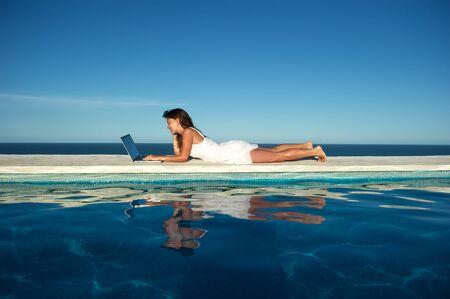 Pretty woman enjoying the sea view of the swimming pool with her laptop in Arraial dAjuda, Bahia, Brazil Stock Photo