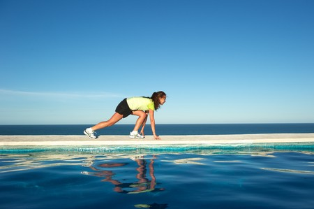 Woman doing exercises on the wall of a swimming pool with sea view in Arraial dAjuda, Bahia State, Brazil